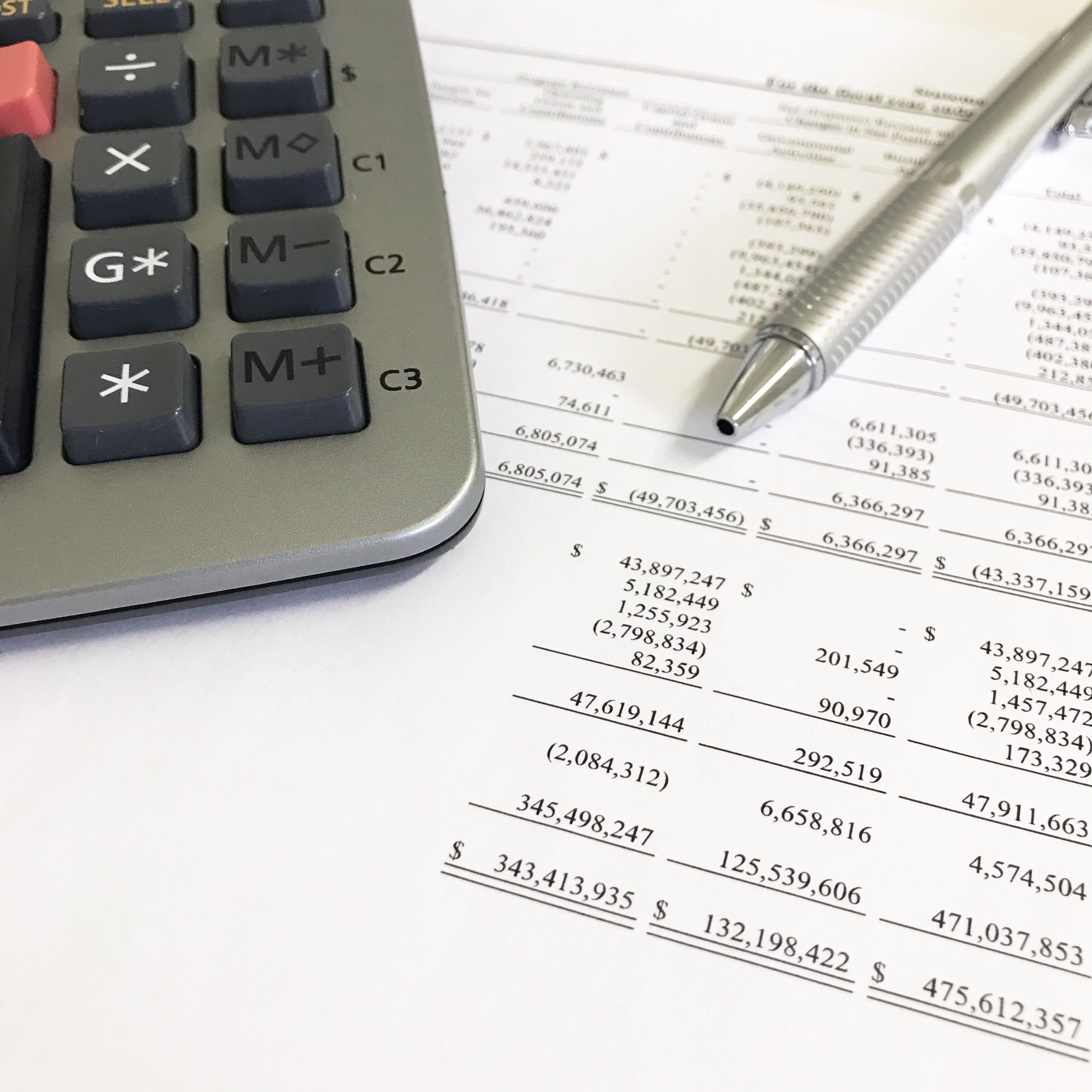 Image of a calculator and pen on top of a financial statements